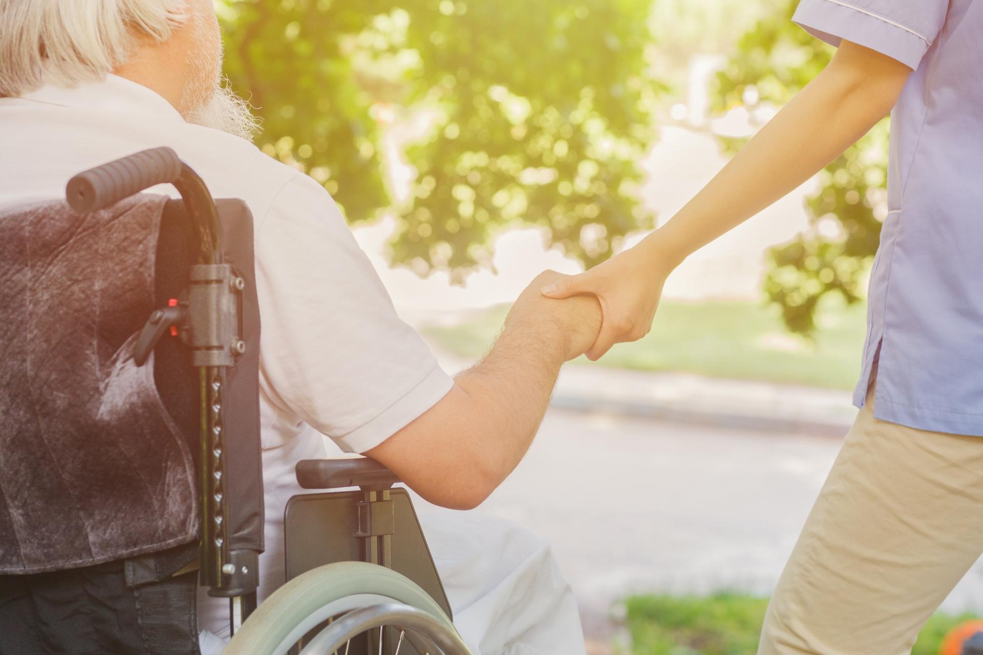 車椅子の高齢男性と手をつなぐ介護福祉士4の写真